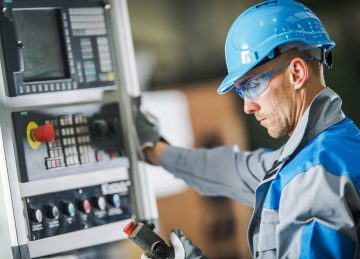 Caucasian CNC Machine Operator Wearing Blue Hard Hat and Safety Glasses. Industrial Concept.